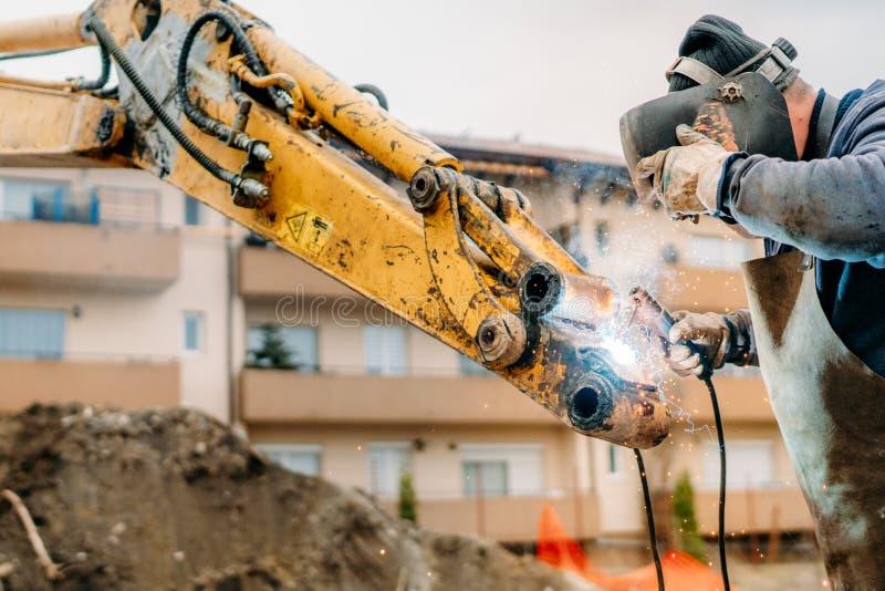 Escavatore della riparazione del meccanico sul cantiere immagini stock