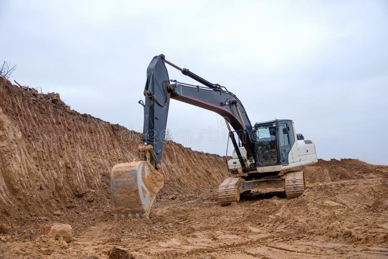 Escavatore durante lavori in terraferma in cantiere Sbarco del terreno per la fondazione e per la posa di condutture fognarie fotografie stock libere da diritti
