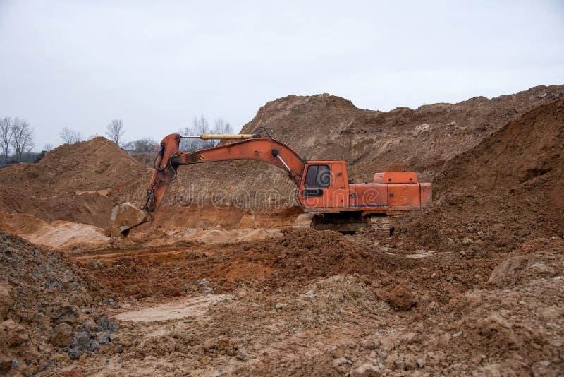 Escavatore durante lavori in terraferma in cantiere Sostegno alla ricerca di un terreno per la fondazione fotografia stock