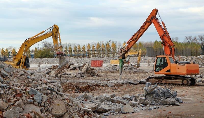 Escavatori che smantellano una grande vecchia zona industriale per una ricostruzione in un'area commerciale futura immagine stock libera da diritti