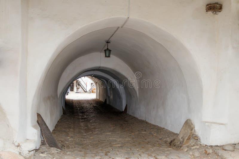 Escave um túnel na parede protetora entre o pátio exterior e interno da igreja fortificada Prejmer na cidade de Prejmer em Romêni imagem de stock