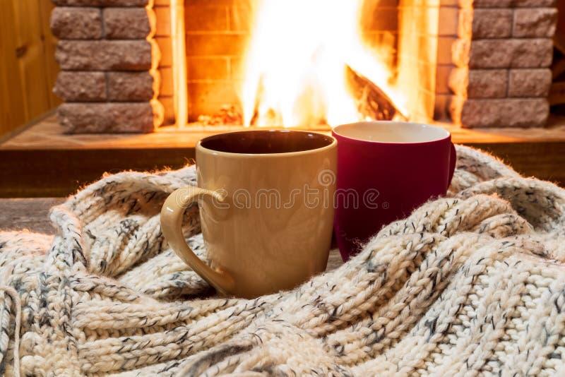 Escena acogedora cerca de la chimenea con dos tazas de té caliente y de bufanda caliente acogedora foto de archivo libre de regalías
