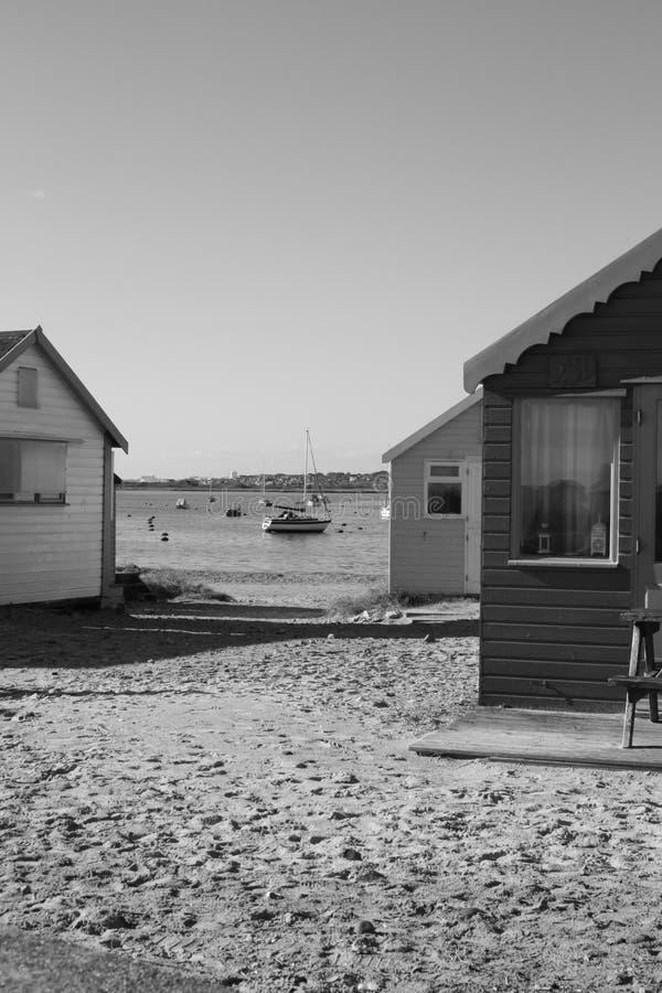Escena blanco y negro de la playa con las chozas de la playa imagenes de archivo