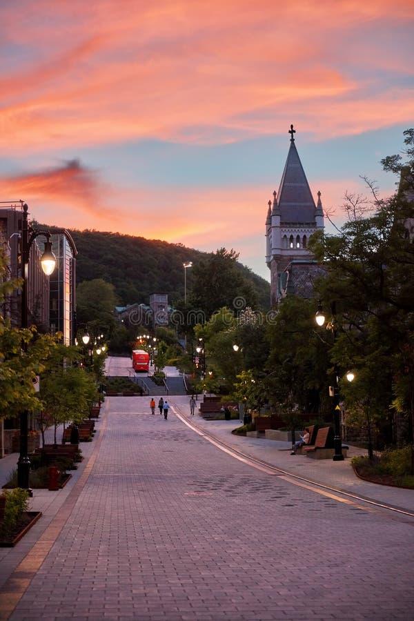 Escena cambiante hermosa de la puesta del sol en la calle de Mctavish Gente que camina en el guijarro, mout real y la torre de la foto de archivo