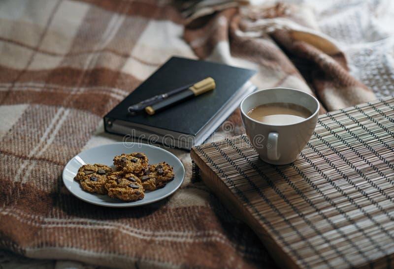 Escena con café en la tabla, galletas y un cuaderno imagen de archivo
