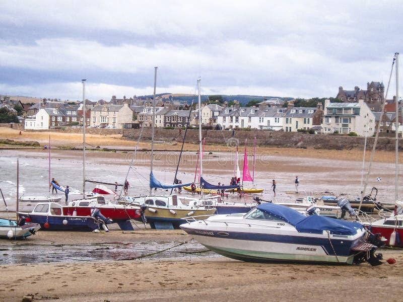Escena costera escocesa con los balandros de la navegación en la playa durante la bajamar imagenes de archivo