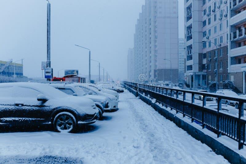 Escena de la calle de la ciudad de la nieve del invierno Coches nevados en la calle del invierno en Rusia imagen de archivo