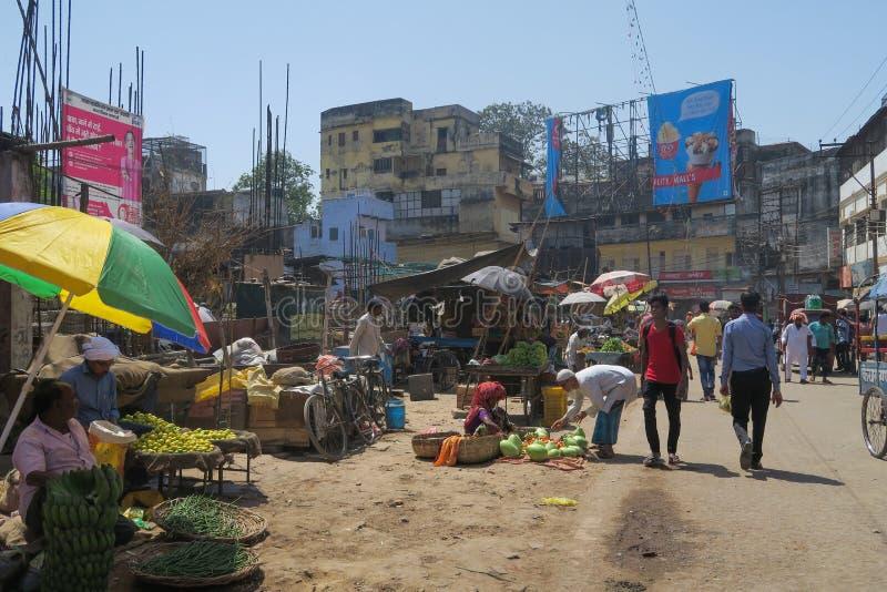 Escena de la calle de mercado en Varanasi, Uttar Pradesh con los paraguas y las porciones coloridos de gente fotos de archivo
