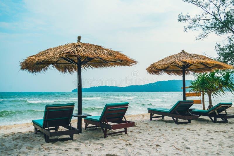 Escena de la calma de la playa con los sunbeds y los paraguas de la paja debajo de las palmas de coco cerca del mar del Caribe Pa imagen de archivo