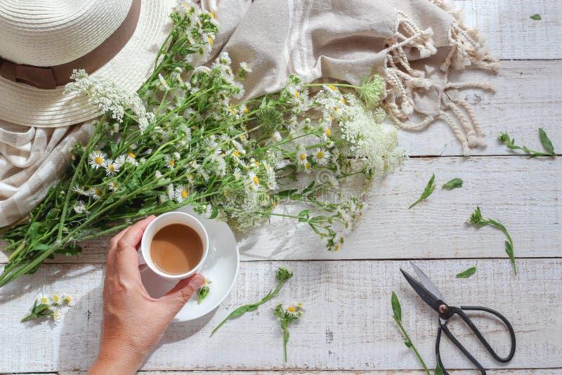 Escena de la mañana del verano con la mano de las flores salvajes, del sombrero y de una mujer que sostiene una taza de café fotografía de archivo libre de regalías