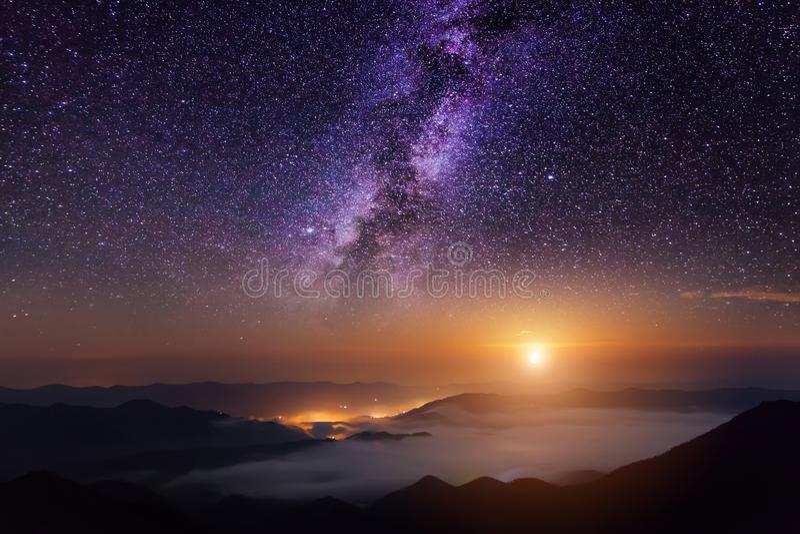 Escena de la montaña con el cielo crepuscular, la luna y las estrellas brillantes de la vía láctea fotografía de archivo libre de regalías