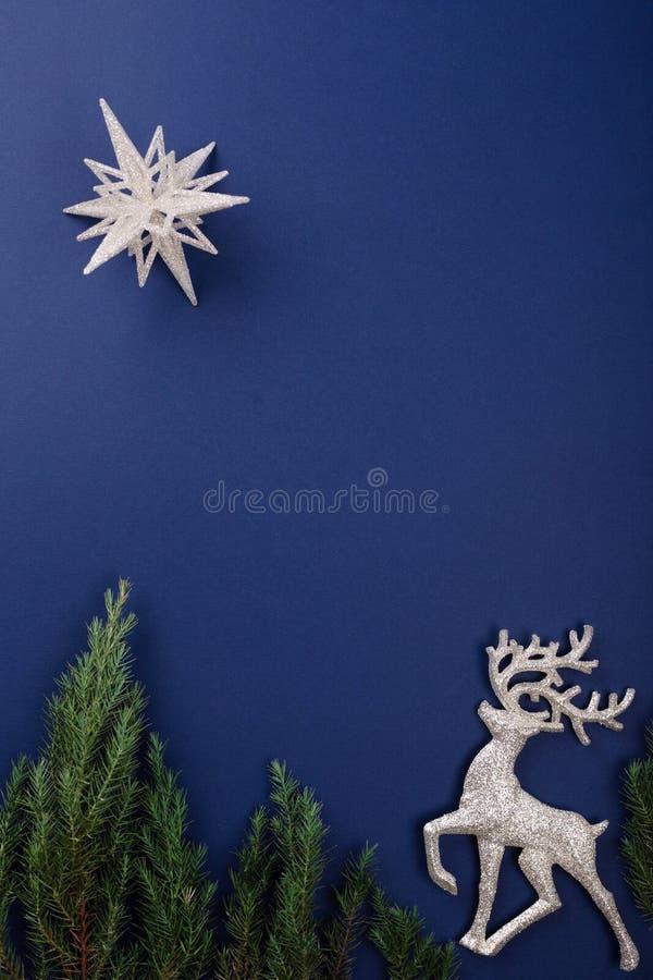 Escena de la Navidad con el reno en fondo azul marino imagen de archivo