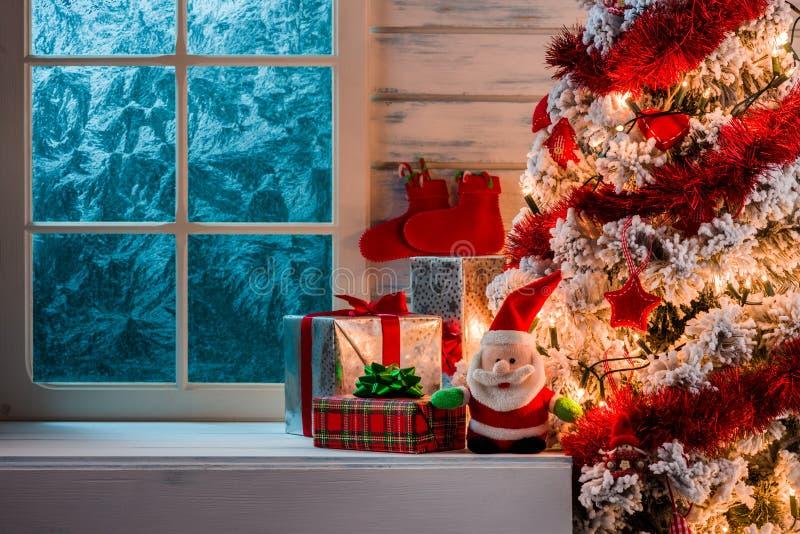 Escena de la Navidad con los regalos del árbol y la ventana congelada foto de archivo