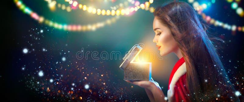 Escena de la Navidad Mujer joven morena de la belleza en caja de regalo de la abertura del traje del partido foto de archivo libre de regalías