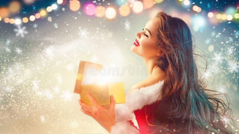 Escena de la Navidad Mujer joven morena de la belleza en caja de regalo de la abertura del traje del partido foto de archivo