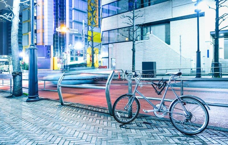 Escena de la noche con la bicicleta parqueada y el coche que apresura borroso en fotografía de archivo