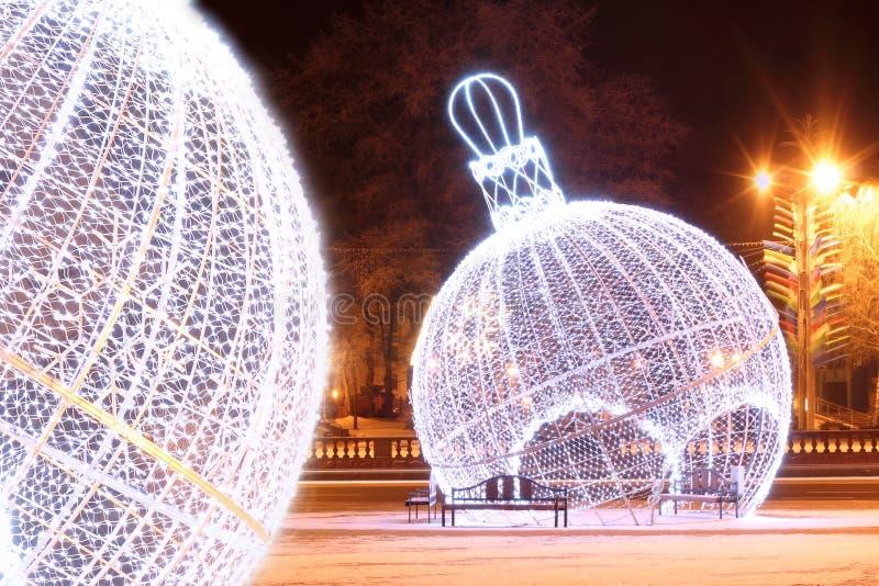 Escena de la noche con las bolas iluminadas de la Navidad fotografía de archivo