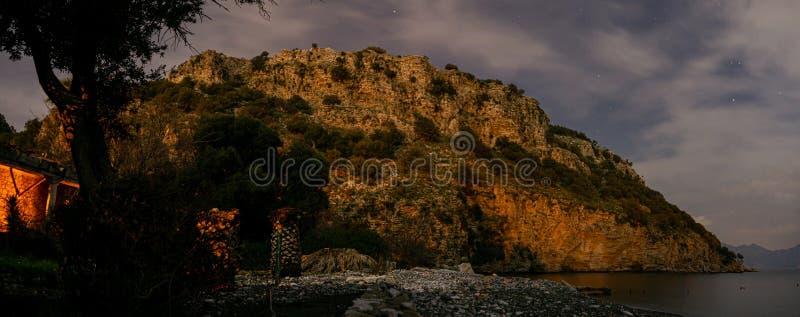 Escena de la noche con la montaña y la costa costa Cielo nublado imágenes de archivo libres de regalías