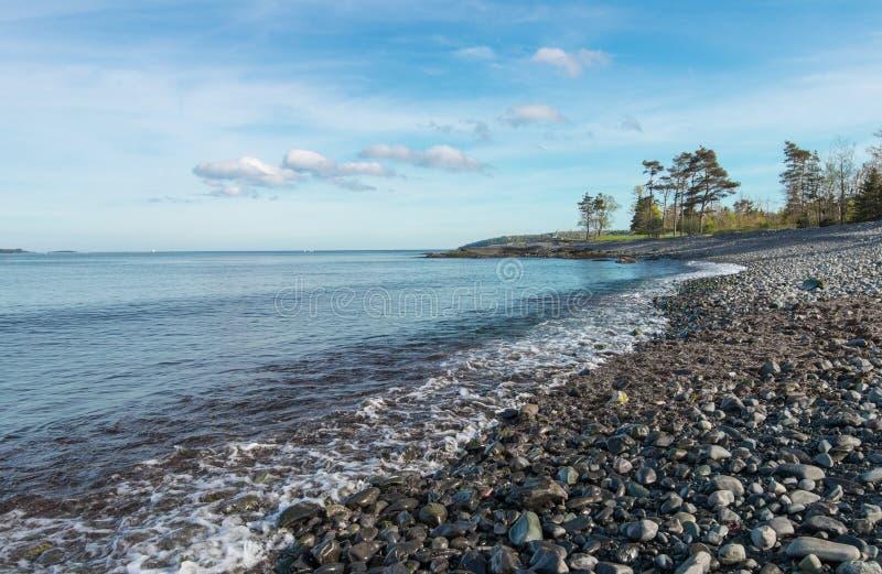 Escena de la orilla por completo de guijarros en la costa costa imagen de archivo libre de regalías