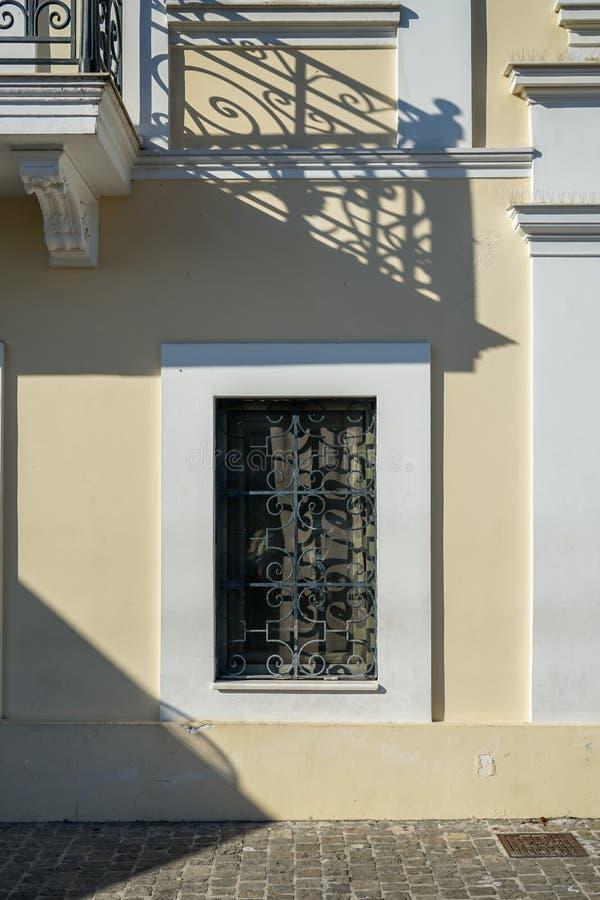 Escena de la ventana y del balcón urbanos hermosos de la fachada del edificio con la sombra de la barandilla del arrabio en pintu foto de archivo