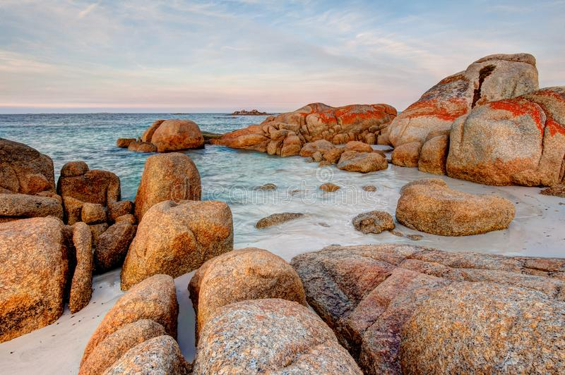 Escena de los cantos rodados gigantes de la roca del granito cubiertos en liquen anaranjado y rojo en la bahía de fuegos en Tasma foto de archivo libre de regalías