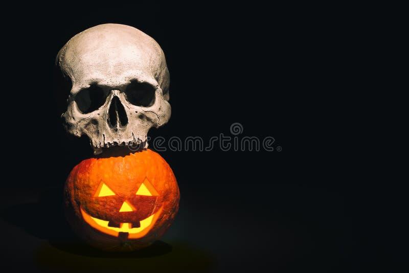 Escena de Víspera de Todos los Santos Cráneo humano en la calabaza de Halloween en fondo del negro oscuro Espacio libre para su t imagen de archivo libre de regalías