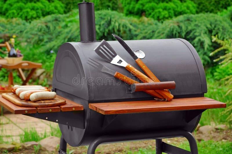 Escena del Bbq del fin de semana del verano con la parrilla del carbón de leña en el patio trasero fotos de archivo