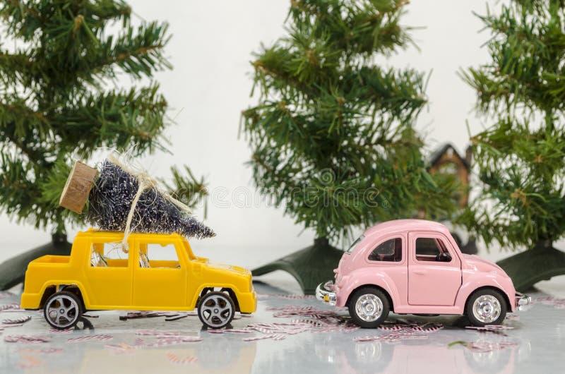 Escena del camino con un coche amarillo que lleva un árbol de navidad detrás del coche rosado imagen de archivo