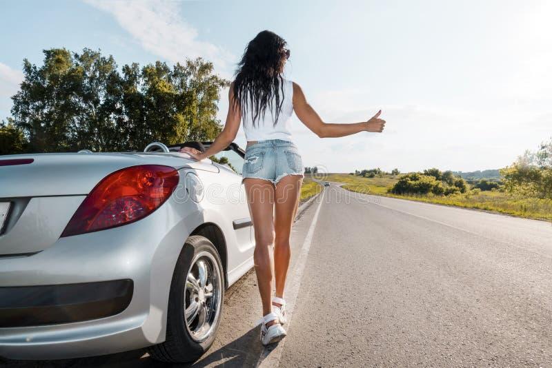Escena del camino: situación morena atractiva de la muchacha cerca de su coche quebrado y autoestop Visi?n trasera Ran Out del ga imágenes de archivo libres de regalías