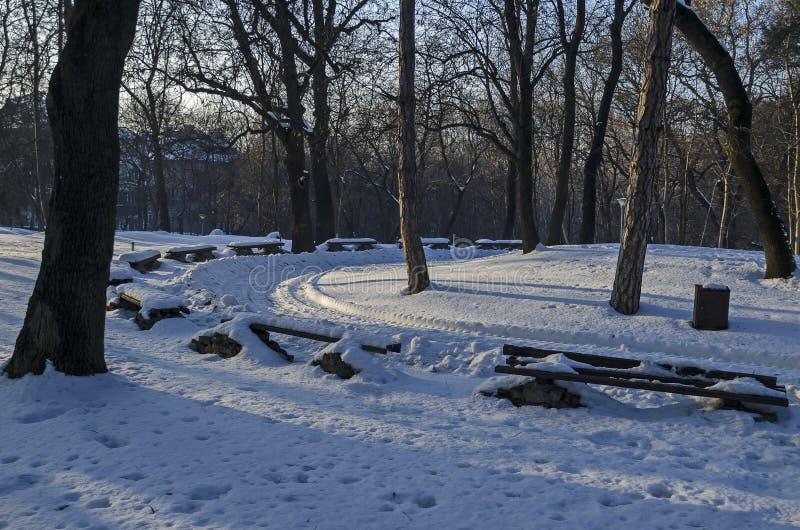 Escena del invierno con el banco de parque, Sofía foto de archivo