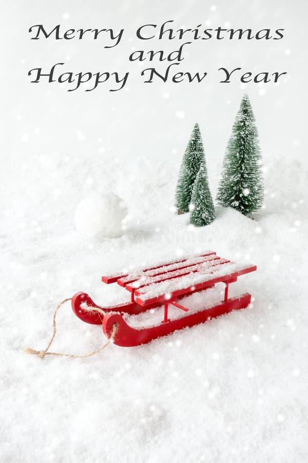 Escena del invierno con el trineo en nieve, bola de nieve y abetos imagenes de archivo
