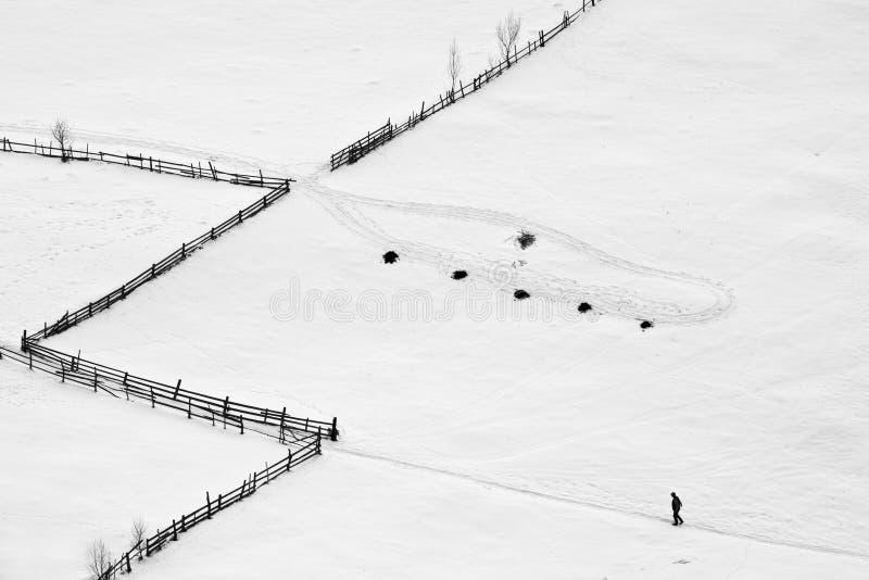 Escena del invierno con un hombre que recorre en su camino foto de archivo