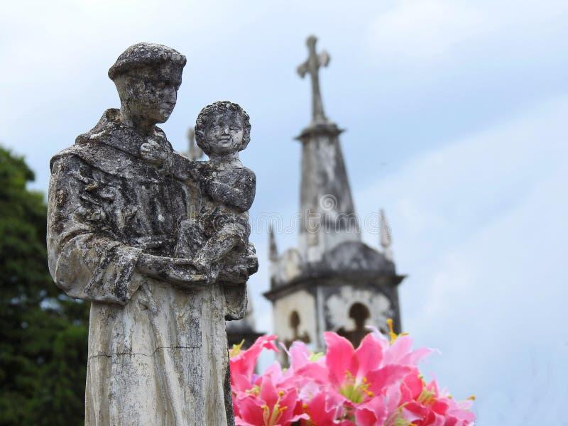 Escena en un cementerio: estatua de piedra de un santo que lleva al bebé Jesús fotos de archivo libres de regalías