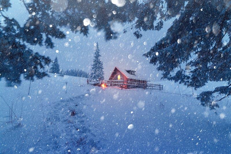 Escena fantástica con la casa nevosa en la igualación del bosque foto de archivo