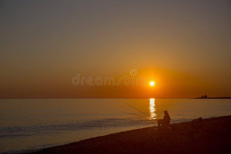 Escena hermosa con la silueta del pescador con la barra que se sienta en la playa del mar fotografía de archivo libre de regalías