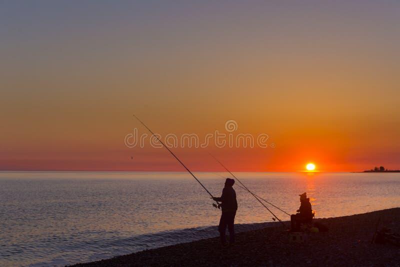Escena hermosa con la silueta del pescador con la barra que se sienta en la playa del mar imagenes de archivo
