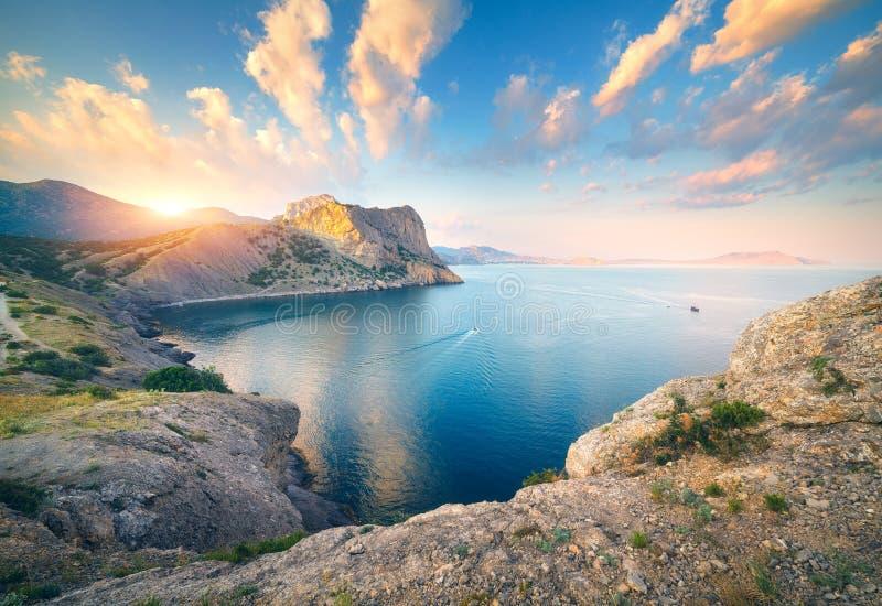 Escena hermosa con las montañas, mar azul, altas rocas fotos de archivo