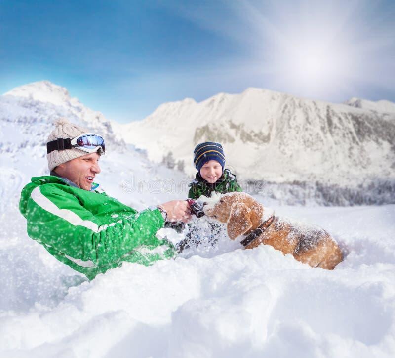 Escena linda de la familia: el padre y el hijo juegan con el perro durante la montaña imagen de archivo