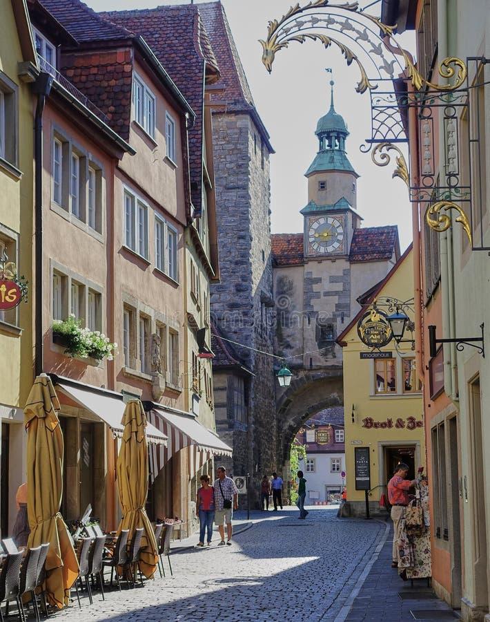 Escena medieval de la calle con la torre y las tiendas del reloj para los turistas foto de archivo libre de regalías