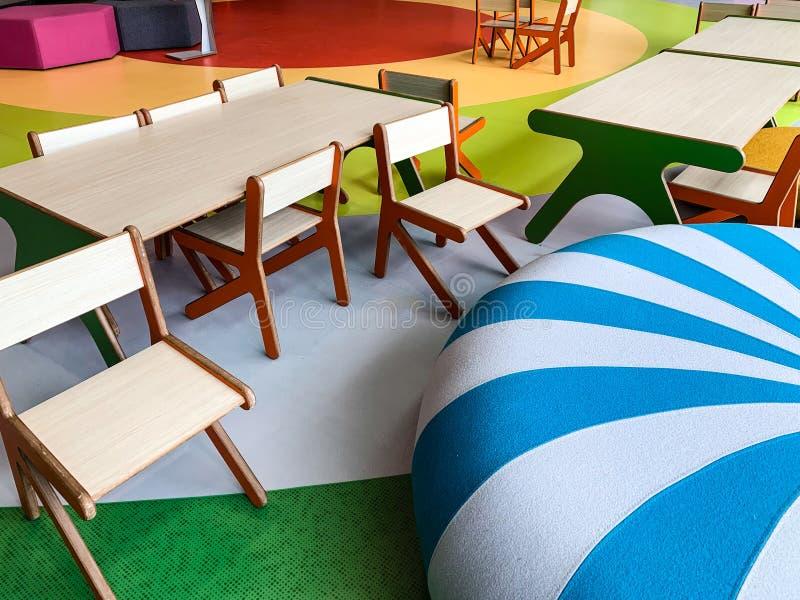 Escena moderna y colorida con las sillas y las tablas para los niños en una sala de espera o un terminal público Concepto amistos imagenes de archivo
