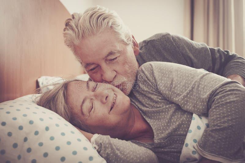 Escena preciosa casera con los pares de besarse mayor en el dormitorio en la ma?ana lista para despertar y para comenzar el d?a j foto de archivo
