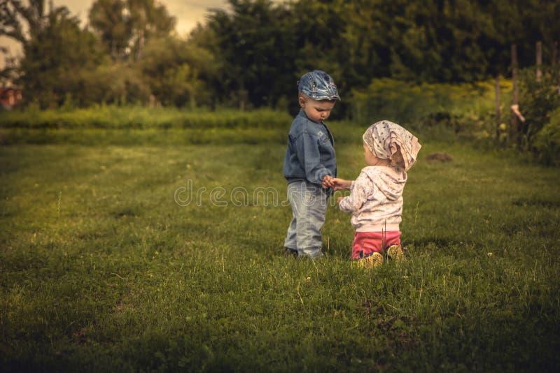 Escena romántica con el par de los niños muchacho y muchacha que se sostienen con las manos en la puesta del sol en el campo rura imágenes de archivo libres de regalías