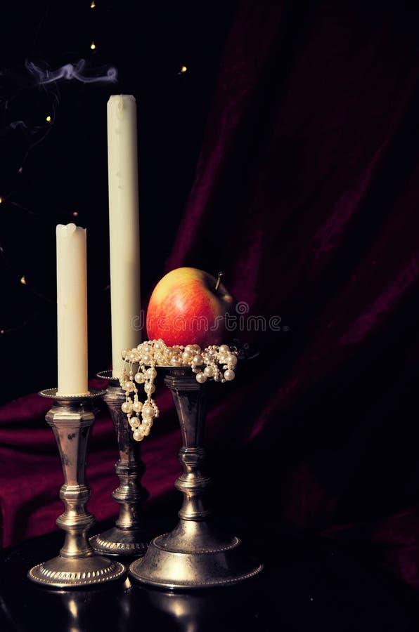 Escena romántica con las velas y la manzana foto de archivo