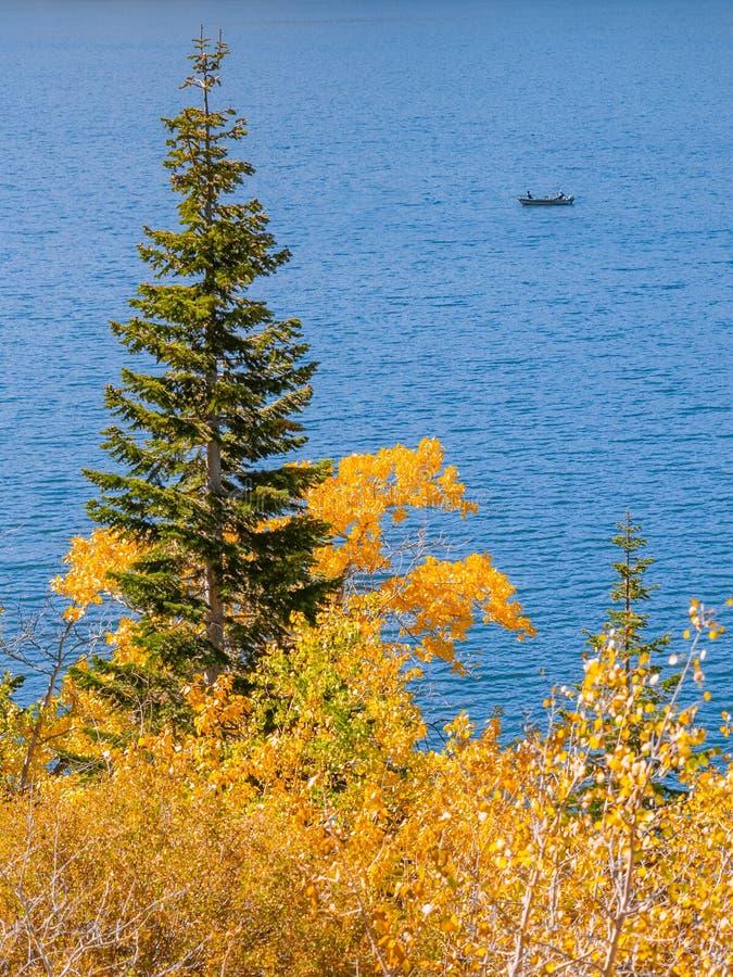 Escena serena del otoño con el barco de pesca en un lago de la montaña imagen de archivo
