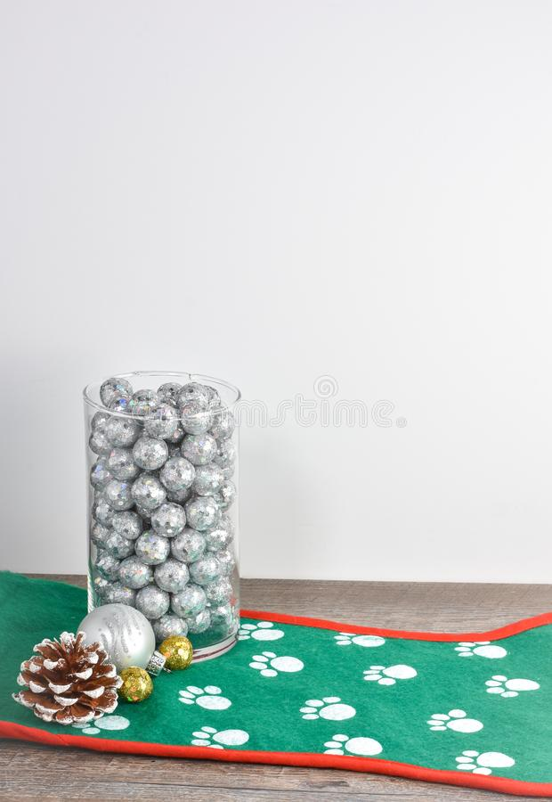Escena simple con los ornamentos, cono helado del pino, vidrio de la Navidad fotografía de archivo