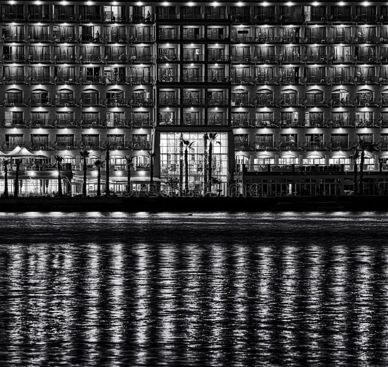 Escena urbana de la noche con reflexiones en un agua, ciudad de la noche con reflexiones en el agua, foto urbana del fragmento de fotografía de archivo