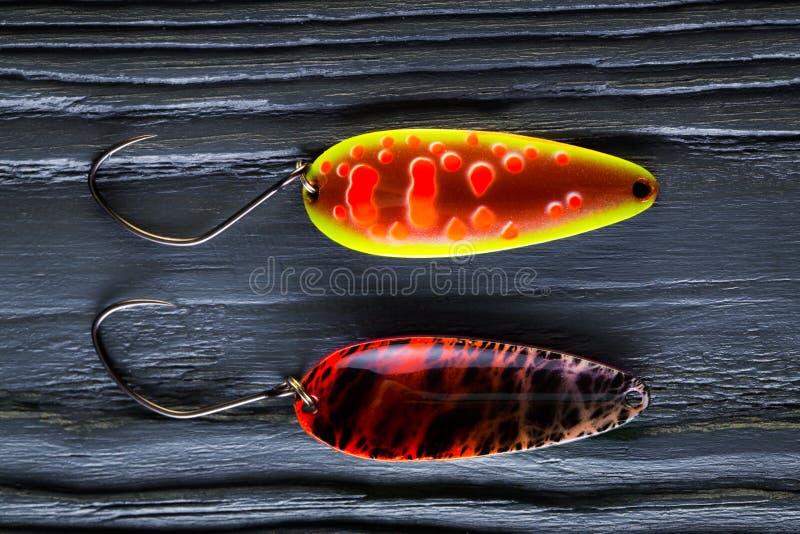 Esche della trota Esche di cucchiaio su fondo di legno nero fotografia stock