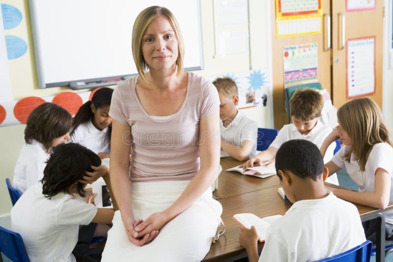 ESchoolchildren y su lectura del tacher en clase imagen de archivo