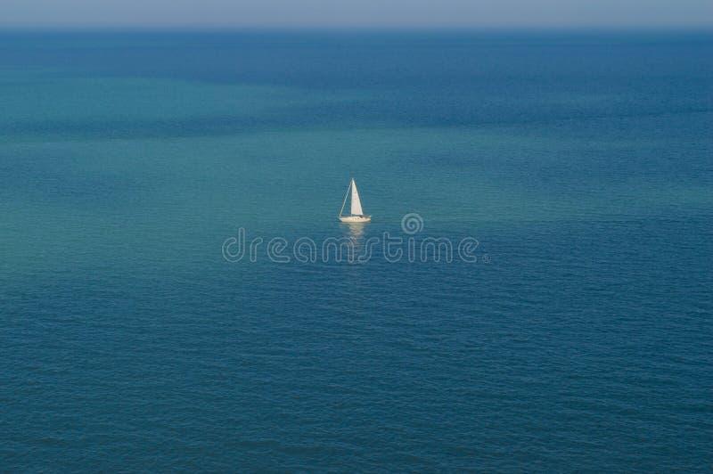 Escoja el barco de navegación blanco-navegado en el medio del océano rodeado por el agua azul profunda fotos de archivo