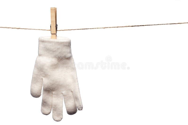 Escoja el guante blanco del invierno que cuelga en una cuerda para tender la ropa imagen de archivo libre de regalías